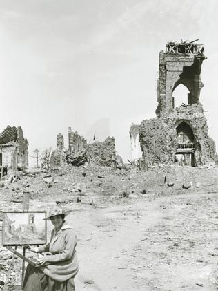Australian artist Evelyn Chapman captured by a photographer in front of her easel while painting the ruined town of Villers-Bretonneux in France. Picture: Supplied.