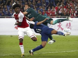 Chelsea's Pedro, foreground, collides with Arsenal goalkeeper David Ospina during the first half of their friendly soccer match in Beijing, Saturday, July 22, 2017. (AP Photo/Mark Schiefelbein)