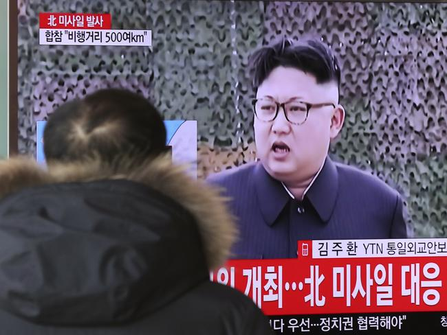 """A man watches a TV news program showing a file footage of North Korean leader Kim Jong Un with letters reading: """"The North fired a missile"""" at the Seoul Train Station in Seoul. Picture: AP."""