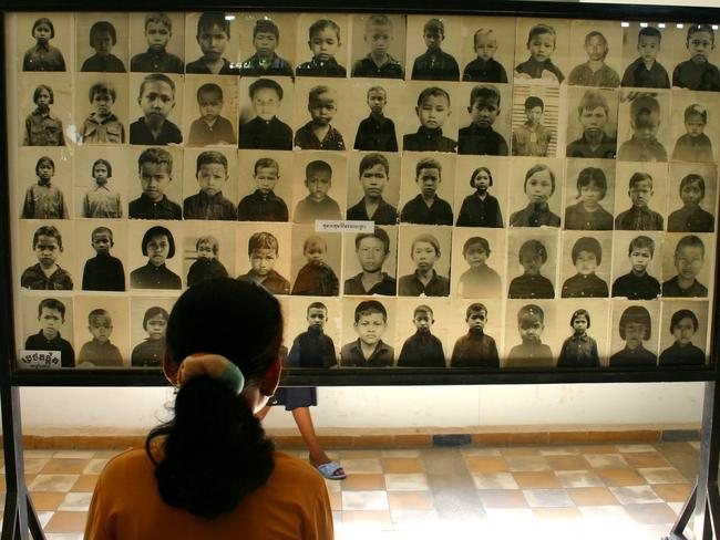 Schoolgirl with photographs of murdered at the Tuol Sleng (S-21) Genocide Museum in Phnom Penh.