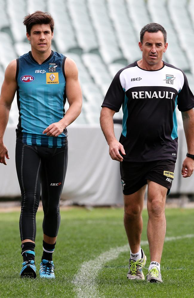 Angus Monfries walks the boundary line with Port Adelaide's Head of Rehabilitation Jarrod Egan. Picture: Sarah Reed