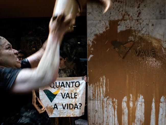 A woman throws muddy water on the facade of Brazilian mining company Vale headquarters next to a sign reading 'How much does a life cost?' in November last year.