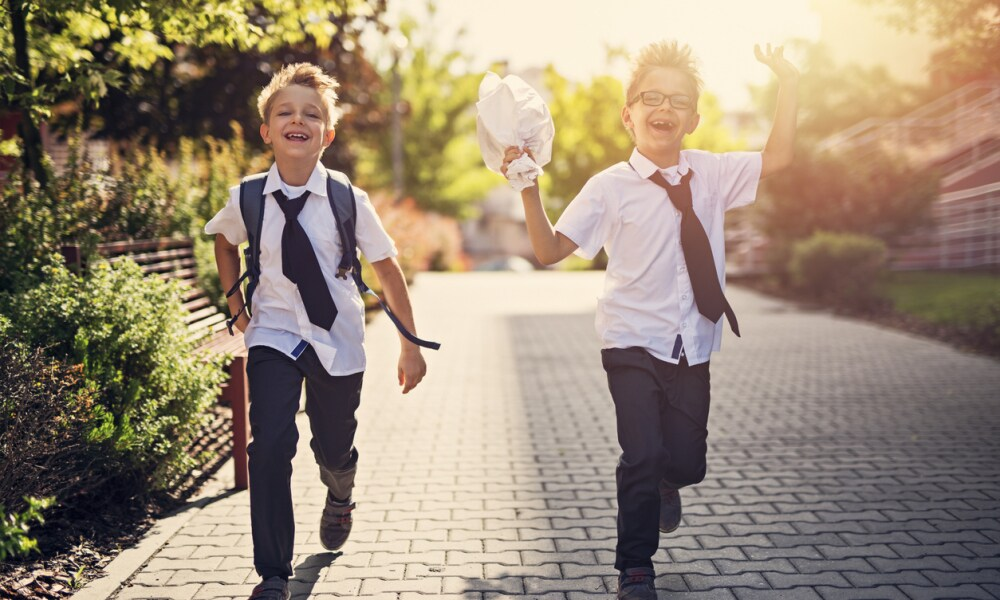 Two happy little boys walking in residential area walkway. Little brothers are going to school in the morning.