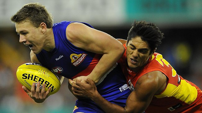 GOLD COAST, AUSTRALIA - MAY 18: Jack Macrae of the Bulldogs is tackled by Aaron Hall of the Suns during the round eight AFL match between the Gold Coast Suns and the Western Bulldogs at Metricon Stadium on May 18, 2013 on the Gold Coast, Australia. (Photo by Matt Roberts/Getty Images)