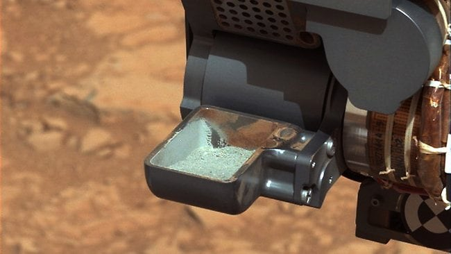 This dated image provided by NASA shows powdered rock in the scoop of the Mars rover Curiosity. The six-wheel rover collected the sample after drilling into a Martian rock.