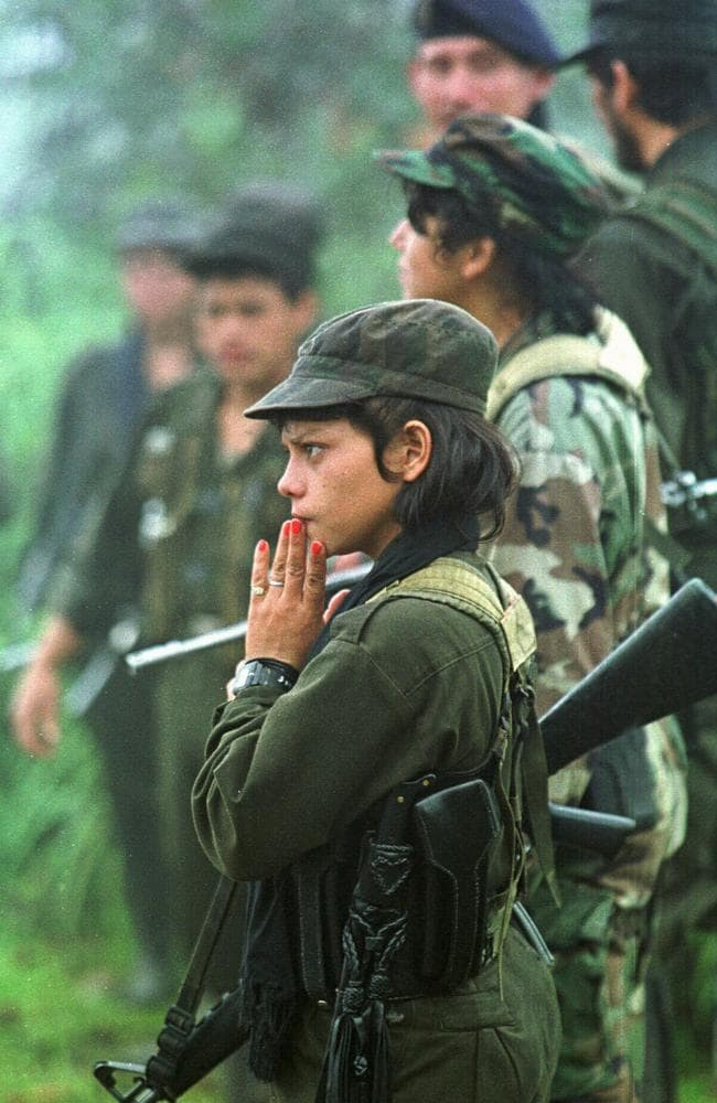 New recruits ... an armed female child Colombian guerrilla waits with other soldiers while patrolling in the Meta region southeast of Bogota, Colombia in 1998. Picture: AP