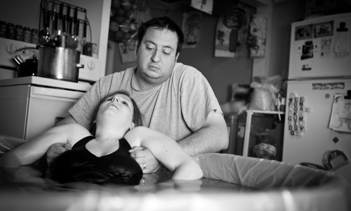 Black and white image of a loving husband supporting and coaching his wife through an intense home birth.