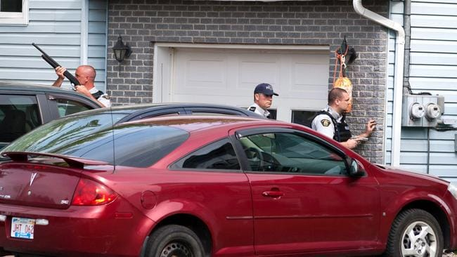 Royal Canadian Mounted Police members surround a house in Moncton, New Brunswick in the search for Justin Bourque. He shot three mounted police dead and injured two others. Picture: AP
