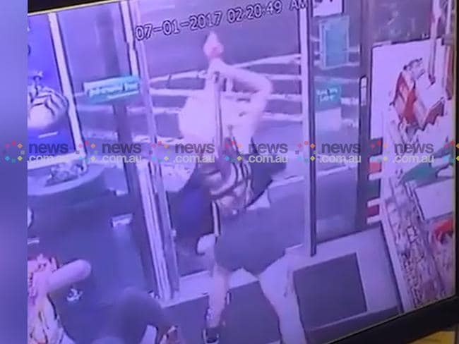 A stunned Mr Rimmer lies reeling on the ground as the woman takes a second swing of the axe at the prostrate Sharon Hacker who has collapsed outside the shop door. Picture: news.com.au