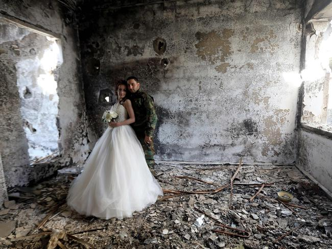 Destruction ... Groom Hassan Youssef is a soldier in Syrian President Bashar al-Assad's army, which took Homs from rebels in November. Picture: AFP/Joseph Eid
