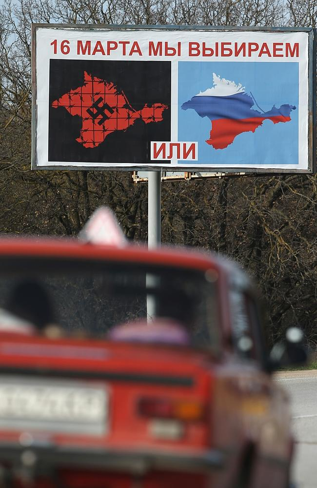 """Bypassed ... a car drives past a billboard that reads: """"On March 16 we will choose"""" and s"""
