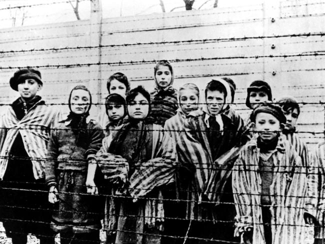 A group of children wearing concentration camp uniforms behind barbed wire fencing in the Auschwitz Nazi concentration camp.