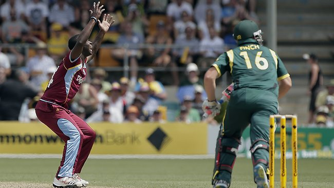 Kemar Roach reacts after an Aaron Finch leading edge lands safely.