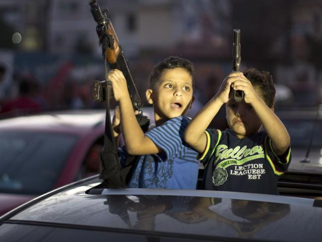 Truce ... Children hold up guns (one with an empty magazine) from a car as Palestinians gather in the streets to celebrate after a deal had been reached between Hamas and Israel.