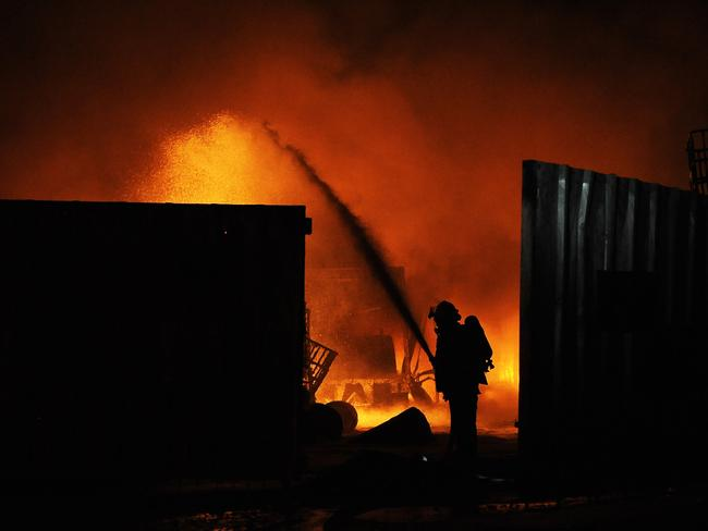 Shot in the dark ... Israeli firefighters extinguish a burning factory hit by an unguided rocket fired from the Gaza strip at an industrial zone in the southern city of Sderot.