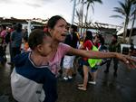 A woman cries as she and her son wait to board a C130 aircraft during the evacuation in Tacloban.