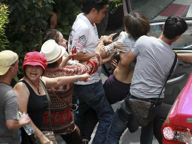 Secret police... Thai plainclothes force a protester in to a taxi during an anti-coup demonstration. Picture: Wason Wanichakorn