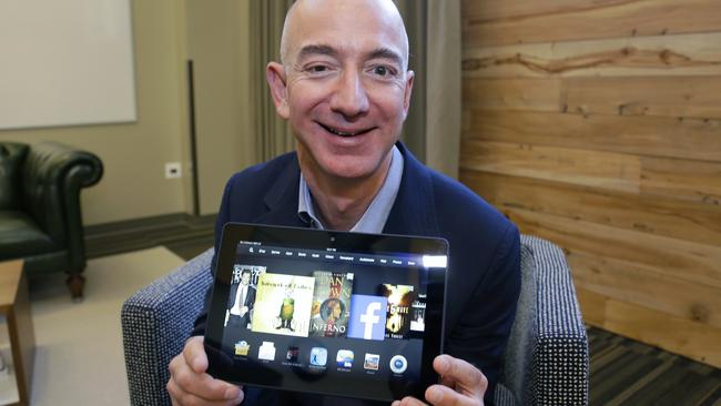 Amazon CEO Jeff Bezos pictured with a Kindle. The company is in a dispute with Hachette Book Group.