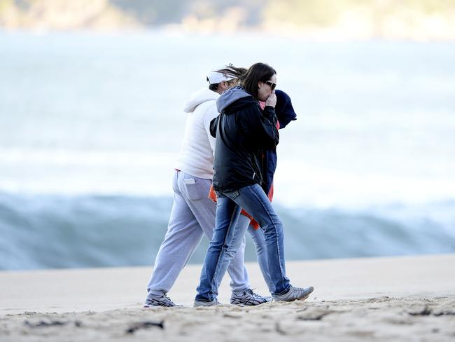 Family members at Pearl Beach on the Central Coast where the boy went missing after being swept into the sea by a rogue wave. Picture: Peter Clark
