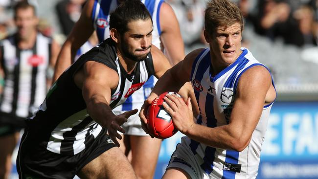 Kangaroo Nick Dal Santo bursts clear of Magpie Brodie Grundy. Picture: Wayne Ludbey