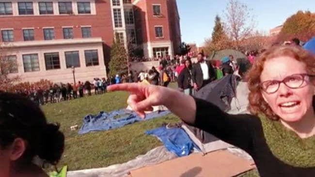 "In this Nov. 9, 2015 frame from the video, Melissa Click, right, an assistant professor in Missouri's communications department, confronts a photographer and later calls for ""muscle"" to help remove him from the protest. (Mark Schierbecker via AP)."
