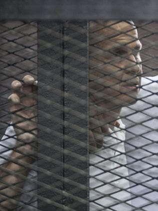 Desperate for freedom ... Al-Jazeera news channel's Australian journalist Peter Greste today, listening to the verdict inside the defendants cage. Picture: Khaled Desouki
