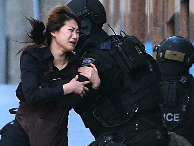 A hostage runs to safety from inside the cafe. Picture: AP Photo/Rob Griffith, File.