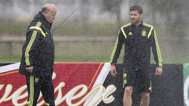 Vicente Del Bosque (L) speaks with midfielder Xabi Alonso as a water sprinkler is turned on.
