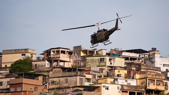 Show of force... A Military Police helicopter flies over the favela on Sunday. Picture: Buda Mendes/Getty Images