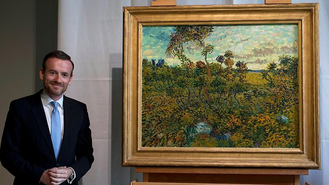 "Van Gogh Museum director Axel Ruger, left, poses next to ""Sunset at Montmajour"" after unveiling the painting by Dutch painter Vincent van Gogh during a press conference at the museum in Amsterdam."