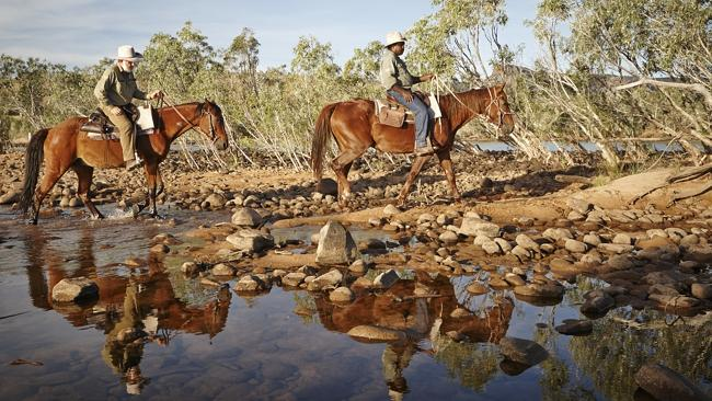 Stockmen Jason Newman and Cyril Yeeda cross the Pentecost River for the cameras to capture the reflections. Picture: Lisa Perkovic