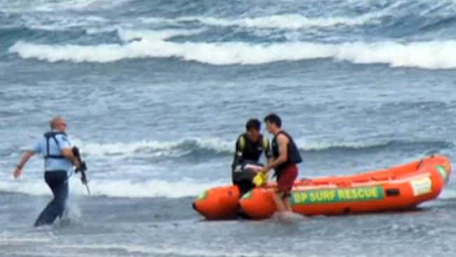 The moment a New Zealand police officer runs towards a rescue boat armed with a rifle after a man was taken by a shark at Muriwal Beach. Picture: Herald New Zealand