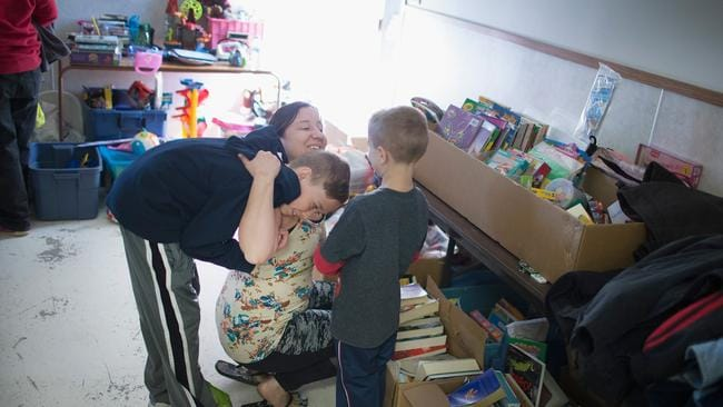 Tara Payne hugs her sons Caleb (L) and Koltyn after they gave her a rose for Mother's Day while the family was searching for necessities at a donation centre established to help evacuees.