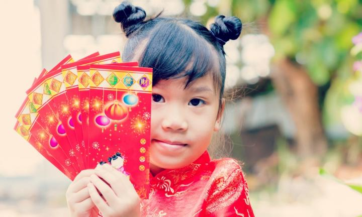 cute girl in chinese dress with red pocket for chinese new year