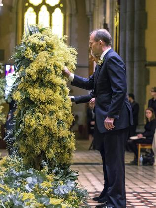 PM Tony Abbott places wattle sprigs on a wreath during the service. Picture: Mark Dadswell