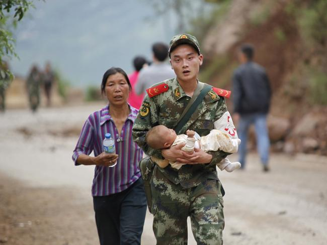Troops dispatched ... a rescuer carries a baby after an earthquake hit an area of Ludian county in China's Yunnan provinc