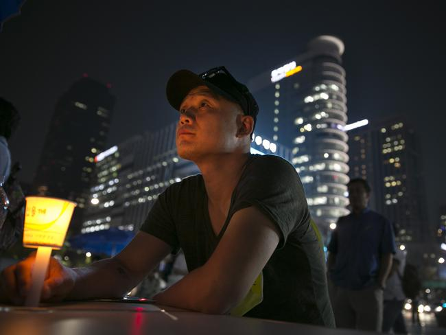 Trial...a man holds a candle as protesters called on the South Korean government to allow a transparent and independent criminal investigation into the ferry disaster. Picture: Getty