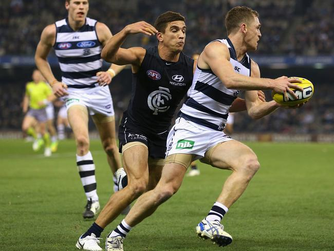 Joel Selwood of the Cats breaks through a tackle by Andrew Carrazzo. Photo by Quinn Rooney