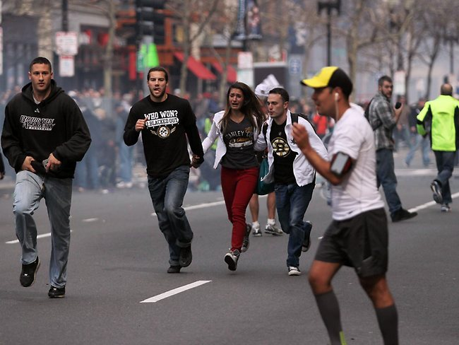 People react to an explosions, shattering the euphoria of the Boston Marathon finish line. Picture: AP