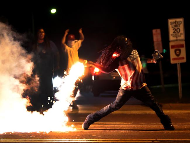 A demonstrator throws back a tear gas container after tactical officers worked to break up a group of bystanders in Ferguson on Wednesday night. AP Photo/St. Louis Post-Dispatch, Robert Cohen
