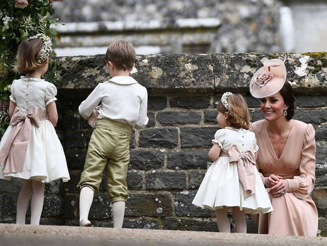 The duchess sits with the children outside the church following the ceremony.