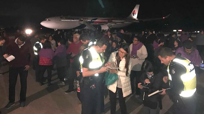 Passengers speaking to officers on the tarmac after coming off the Malaysia Airlines flight. Picture: AFP