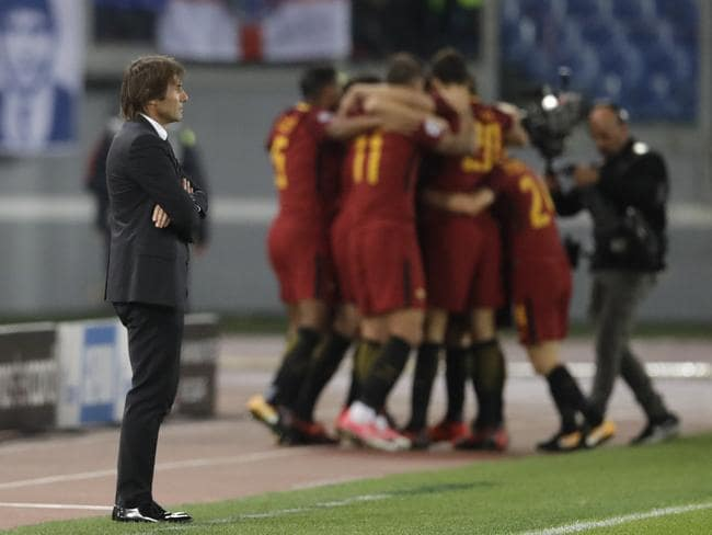 Chelsea coach Antonio Conte stands as Roma players celebrate.