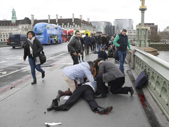 Here's yet another passer-by allowing professionals to get on with the job of treating an injured person on Westminster Bridge. Picture: Reuters/Toby Melville
