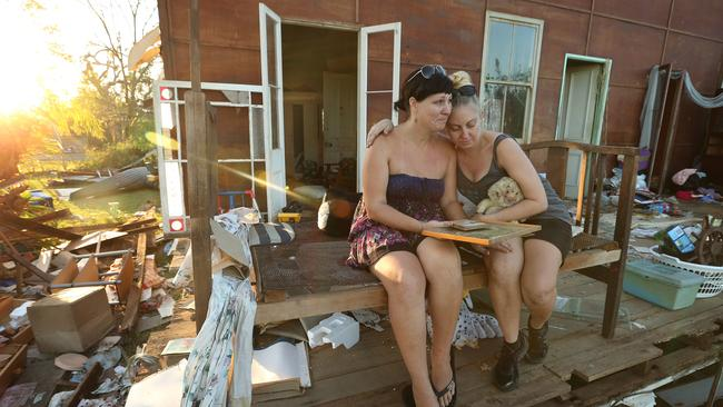Sisters Mel Codd and Emma Codd sit in the ruins of the house they grew up in Yeppoon after the town was hit by the category 3 Cyclone Marcia in 2015.