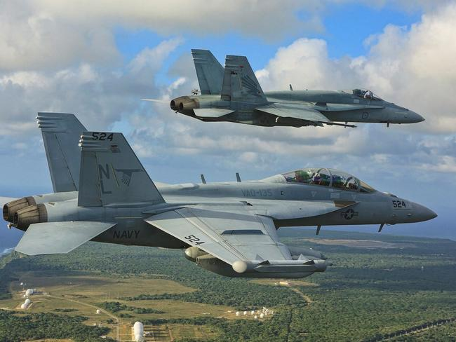 An E/A-18G Growler from the United States Navy (front), and a No 3 Squadron F/A-18 Hornet from the Royal Australian Air Force fly in formation as they return to Andersen Air Force Base. Picture: Commonwealth of Australia