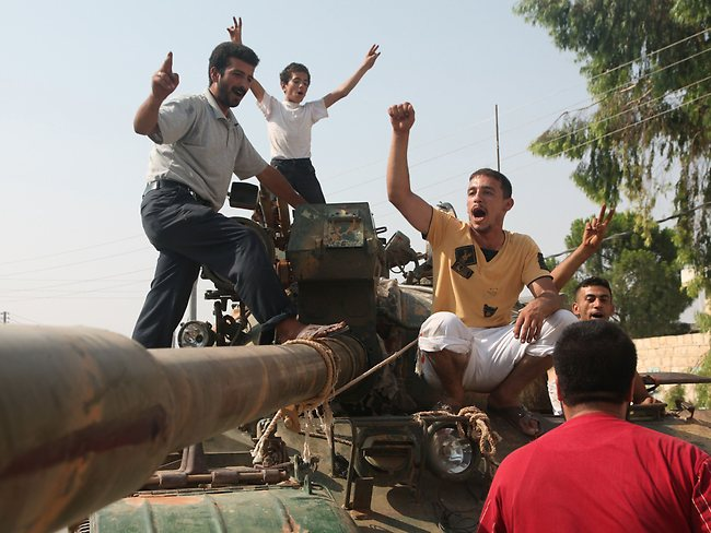 Syrian rebel fighters celebrate on top of a tank captured from the Syrian government forces at a checkpoint in the village of Anadan, about five kilometres northwest of Aleppo.