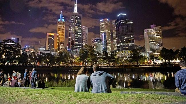 A couple take a break on the banks of the Yarra River during White Night. Picture: Nathan
