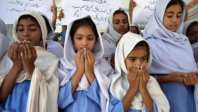Pakistani school girls pray for the recovery of gunshot victim, Malala Yousafzai, in Multan on October 10, 2012. Pakistani doctors removed a bullet from a 14-year-old child campaigner shot by the Taliban in a horrific attack condemned by national leaders and rights activists. The attack took place in Mingora, the main town of the Swat valley in Pakistan's northwest, where Malala had campaigned for the right to an education during a two-year Taliban insurgency which the army said it had crushed in 2009. AFP PHOTO / S.S MIRZA