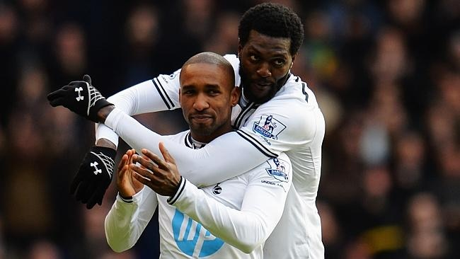 Jermain Defoe and Emmanuel Adebayor share a nice moment.
